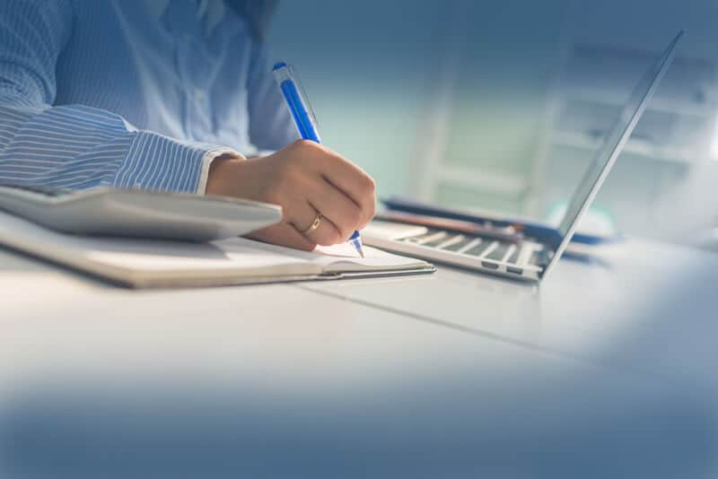 Image of person writing notes next to the laptop